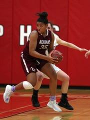 Aquinas' Kayla Jackson spins to the basket against Mendon.