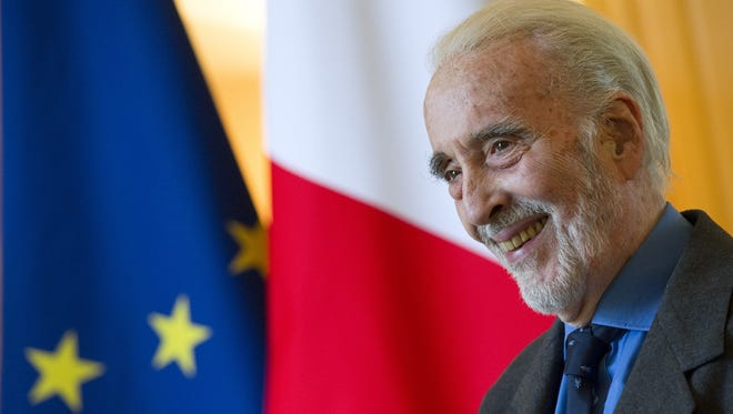 British actor Christopher Lee smiles during a ceremony where he was presented with the Insignia of Commandeur de L'Ordre des Arts et Lettres honouring his contribution to the fields of art and literature at the residence of the French ambassador to Britain Bernard Emie in London on December 16, 2011.