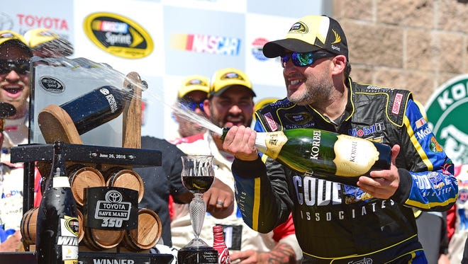Tony Stewart sprays champagne in victory lane after winning Sunday's Toyota/Save Mart 350 at Sonoma Raceway.