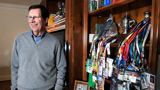 David Poile stands in his office of his Nashville home where a collection of game day and special event passes hang from a shelf along with many of his hockey awards and photographs of his family.