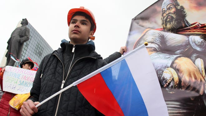 A Pro-Russian activists holds a Russian flag during a rally in Donetsk on March 29, 2014.