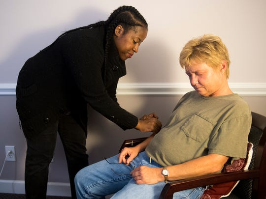 Satori Acupuncture of Knoxville owner and military veteran Nikki Peoples, left, performs acupuncture on a client at her business in Knoxville on Friday, May 25, 2018.