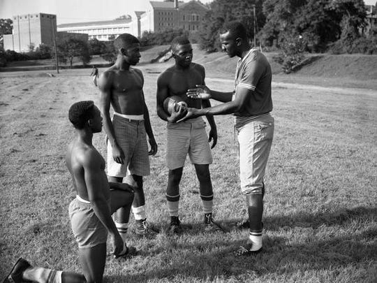 Players from the 1960 FAMU High football team practice without pads during August conditioning drills. Left to right, A. C. Miller, W. Paremore, Sam Lawrence and Coach Bobby Lang.