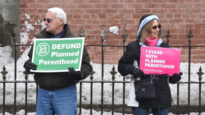 Joe Benigno, left, of Wappingers Falls, and Diane Bearsich, right, of Pawling, stand next to each other while engaging in opposing protests on Church Street in the City of Poughkeepsie.