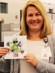 Nancy Apriesnig, human resources consultant with ThedaCare proudly shows off her anniversary yearbook.