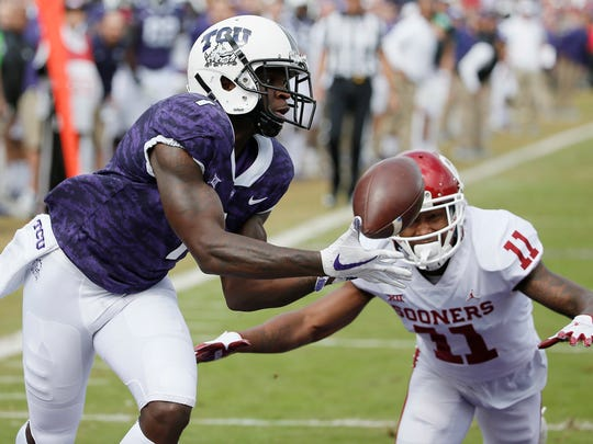 TCU wide receiver Jalen Reagor catches a pass for a touchdown as Oklahoma cornerback Parnell Motley defends during a 2018 game in Fort Worth, Texas.
