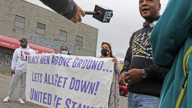 Mark Fisher, right,  speaks to reporters as Black Lives Matter Rhode Island holds a press conference at a parking lot on Broad Street in Providence to discuss recent violence in the city.