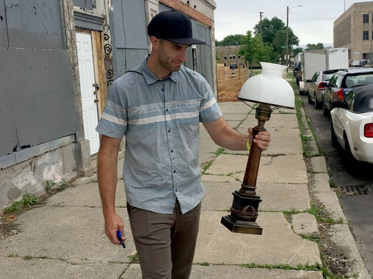 Stephen McGee holds a wooden lamp that used to be on