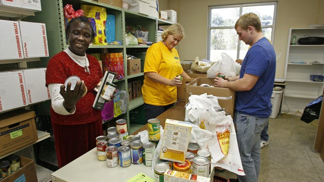 Volunteers Rose Etima, Linda Terpstra and Carter Watson check expiration dates and sort food at the Waukee Area Christian Food Pantry in 2010. The pantry marked its 10th anniversary last week.