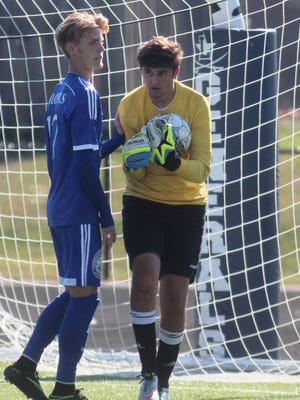 CovCath keeper Thomas Cody snares a loose ball as Michael Vogt, 17, comes in to assist last year.