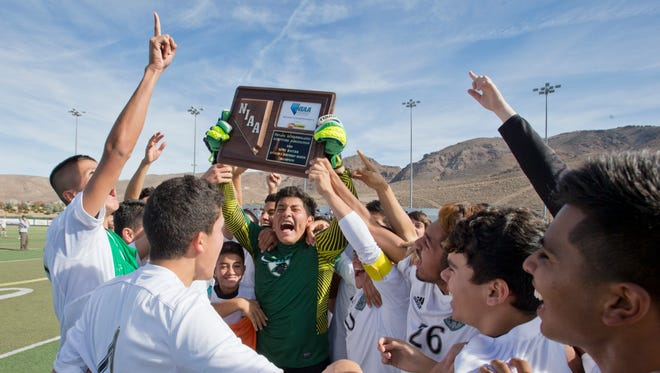 North Valleys goalie Efren Rodriguez holds the trophy as he celebrates with his team after winning the Division I North Region boys soccer championship, 2-0, over Galena at Damonte Ranch High on Saturday.