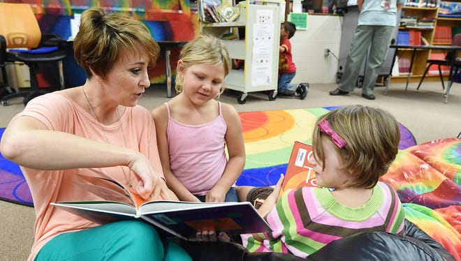 Flippin Elementary School principal Tracie Luttrell, left, reads to kindergarten students, Jozy Rehrig and Willoh Darnell. The Flippin School district in Arkansas started a dyslexia intervention program this summer and has seen significant improvement with students.