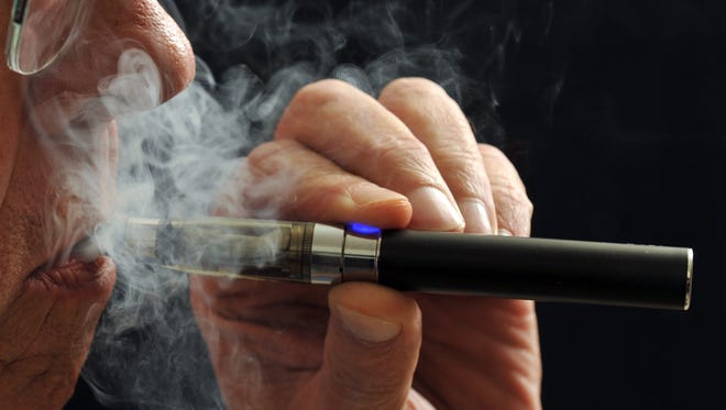 In this Jan. 17, 2014 file photo, a smoker demonstrates an e-cigarette.