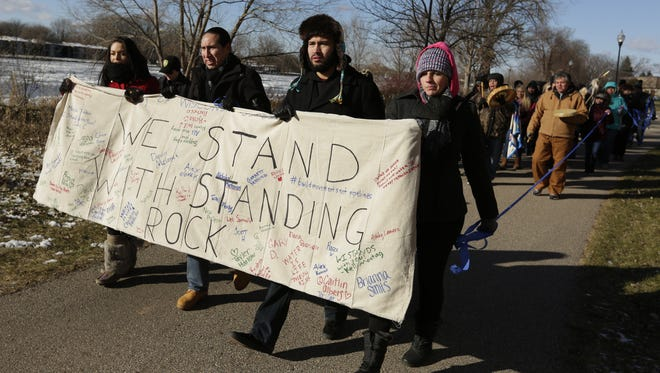 Jessica House, left, Brandon Yellowbird Stevens, Nick Metoxen and Jessica Horn hold the banner as they walk along the Fox River during the march around the UW-Oshkosh campus.  Three student organizations marched and stood in solidarity on the UW-Oshkosh campus in support of the Standing Rock Sioux Tribe and to protest the pipeline that is being built in the region.