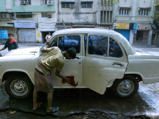 In this photograph taken on May 15, 2006, Indian residents wash a white Ambassador car on the roadside in Calcutta.