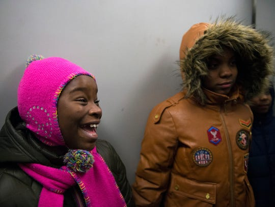 Makhaila Bryant, 10, smiles alongside 12-year-old Darnajah Huff, as they ride the elevator to their apartment to open Christmas presents.