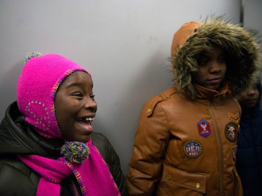 Makhaila, 10, left, smiles alongside her sister Darnajah, 12, as they ride the elevator to their apartment to open Christmas presents Monday, Dec. 18, 2017 in Cherry Hill, New Jersey.