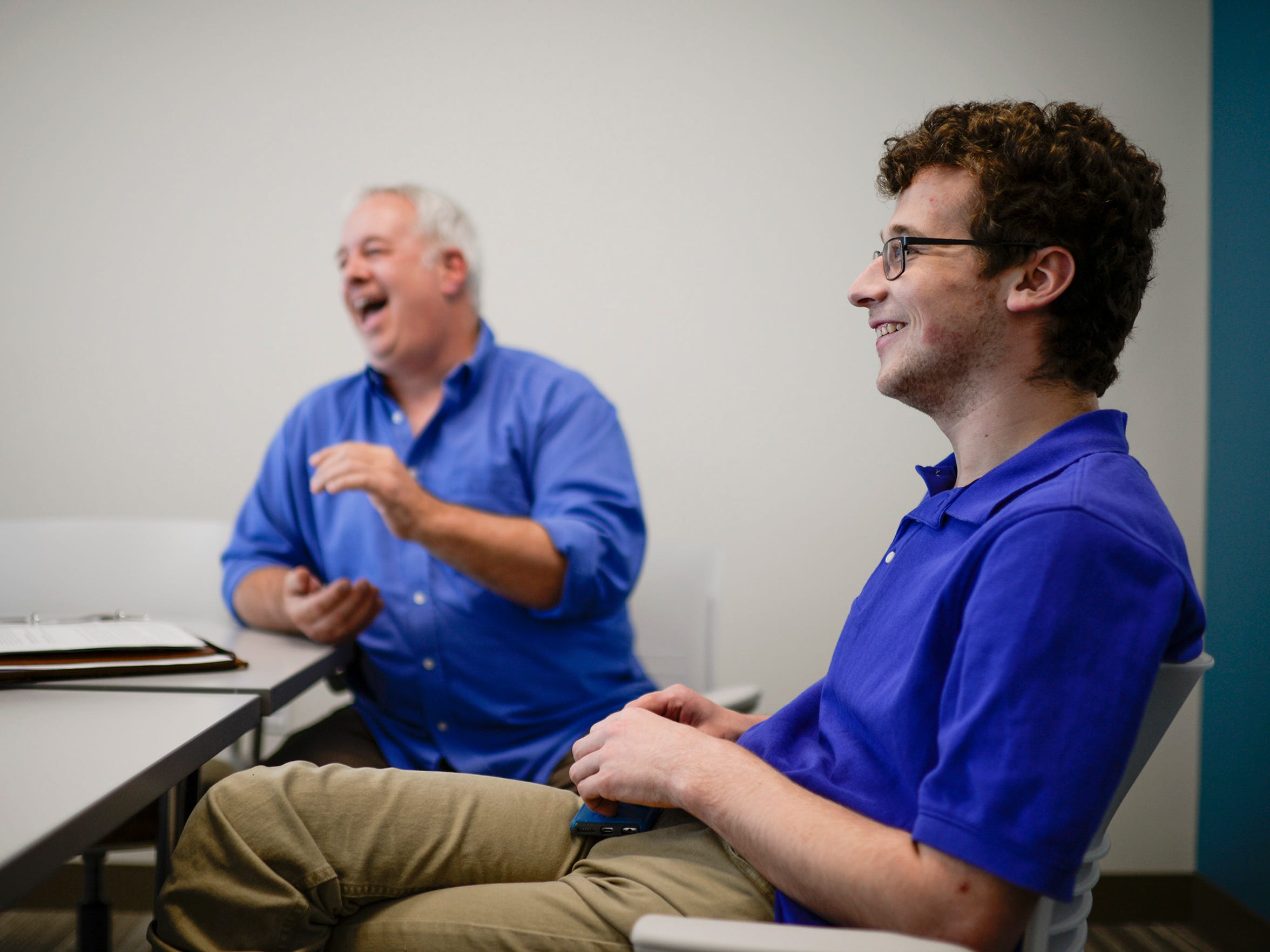 Comedians Harrison Brown, 19, right, and his father Peter Brown share a laugh while discussing their comedy.