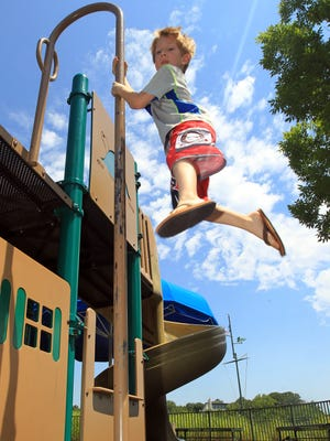 Payton Probst, 6, of Finneytown, zips down the firefighter's pole on the playground at Winton Woods Park. Playground improvements at Winton Woods and Sharon Woods are among the items that park leaders say will be paid for with taxes that would be raised by an upcoming levy.
