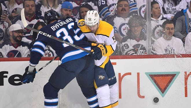 Winnipeg Jets defenseman Dustin Byfuglien (33) slams Nashville Predators left wing Austin Watson (51) into the boards during the first period of Game 3 in the second-round NHL Stanley Cup playoff series at Bell MTS Place in Winnipeg, Manitoba, Canada, Tuesday, May 1, 2018.