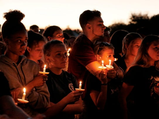 Thousands of mourners attend a candlelight vigil for