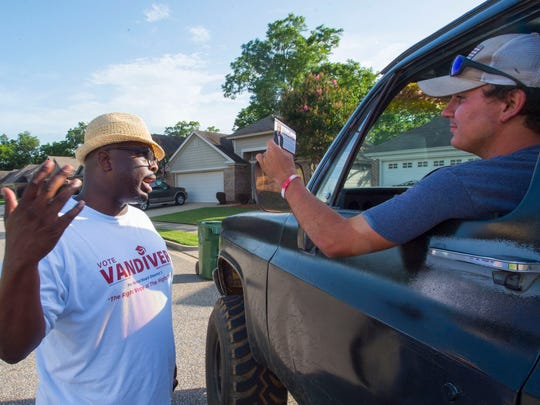 Marcus Vandiver, left, democratic candidate for Montgomery School Board District 1, talks with Collin Denton as campaigns to win the runoff, June 19, 2018, in the Stoney Brook neighborhood in Montgomery, Ala.