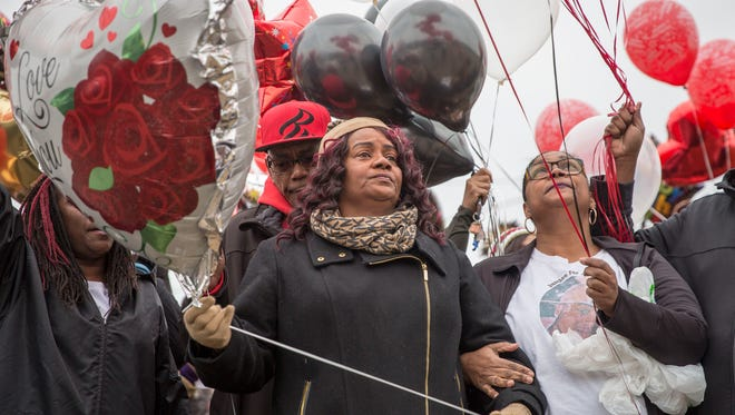 Brenda McCoy stands with family in front of a billboard for Joseph Johnson on Feb. 4 as they release balloons on his birthday. Johnson, McCoy's son, was ambushed outside his southside home last year and killed.