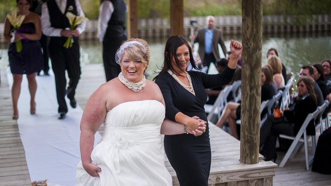 Carla Hester and Brandy Cavitt celebrate as they walk down the aisle following their ceremonial wedding on False River in Louisiana, Saturday, Nov. 12, 2011.