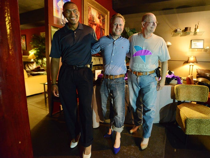 Eric Kellum, Donald Jordan and Captain Mike Holt (left to right) model heels at the official launch party for the Walk A Mile Jackson event at Miss Ollie's Thursday. Walk a Mile Jackson is challenging the men of our community to show their commitment to ending violence against women by walking a mile in a woman?s shoes