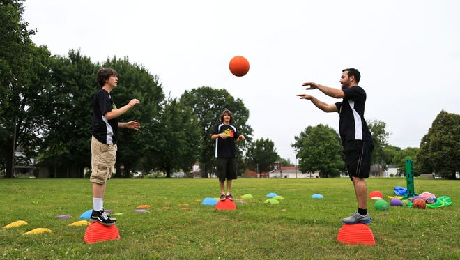 Tim Jones, right, a recreation supervisor with Metro Parks, tosses a ball with Kaelib Ellingsworth, center, and Jarred Bond, left, during a mobile activities program on Rowan Street in Louisville's Portland neighborhood. The mobile program will be traveling to different areas of Louisville where neighborhoods are lacking a recreation program.
