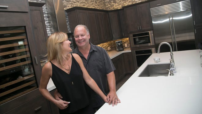 Lisa and Gregg Larson pose for pictures in their home at Enclave at Borgata luxury condos in Paradise Valley on May 9, 2017.
