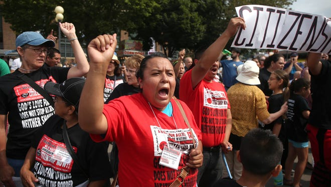 Members of a immigration activist group disrupt a speech by New Jersey Gov. Chris Christie at the Des Moines Register soap box at the Iowa State Fair on Saturday, Aug. 22, 2015, in Des Moines, Iowa.