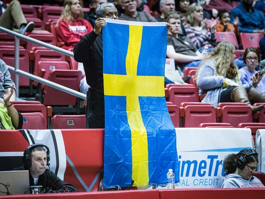 A fan holds up a Swedish flag for Nathalie Fontaine