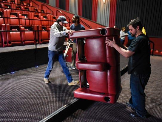 Workers install new DreamLounger recliners Wednesday,