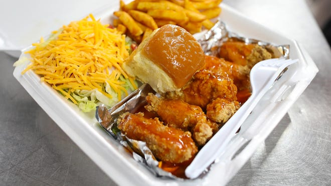 A plate of fried chicken wings with fries and salad from Wayne Head's Southern Kitchen in Gainesville.