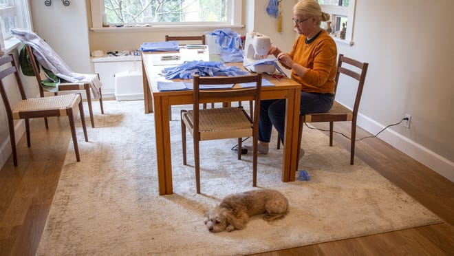Maggie Carlson, a registered nurse who travels frequently on medical missions with the local Give Me Sight Foundation and other eye-care groups, works in her home in March to sew surgical masks with her dog, Coco, close by. [Andy Nelson/The Register-Guard file] - registerguard.com