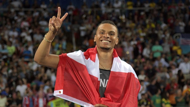 Aug 14, 2016; Rio de Janeiro, Brazil;  Andre De Grasse (CAN) celebrates after placing third during the men's 100m final in the Rio 2016 Summer Olympic Games at Estadio Olimpico Joao Havelange.