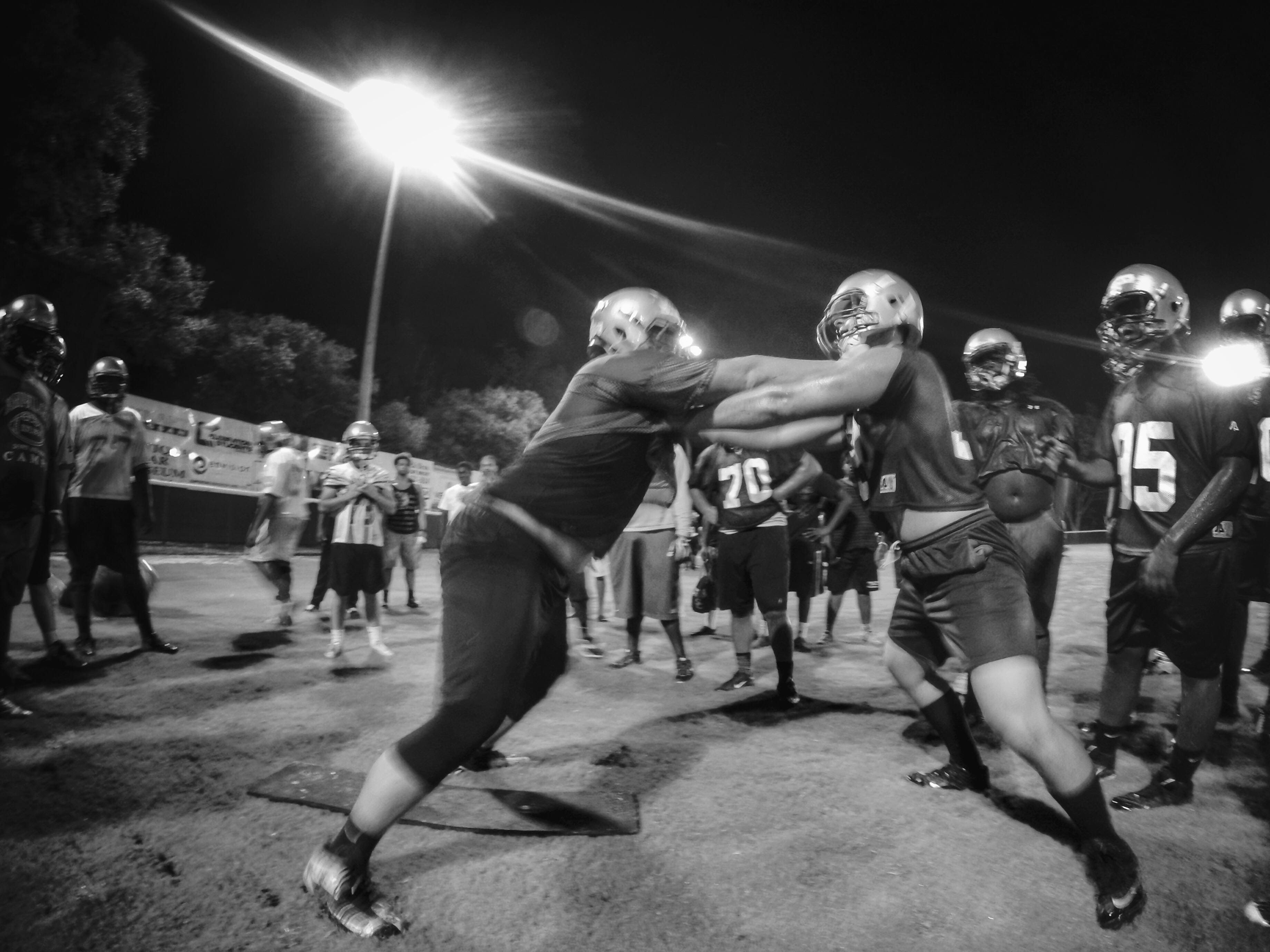Lincoln offensive lineman Tom Moss (left) gets into a contact drill during the Trojans' Midnight Madness practice.