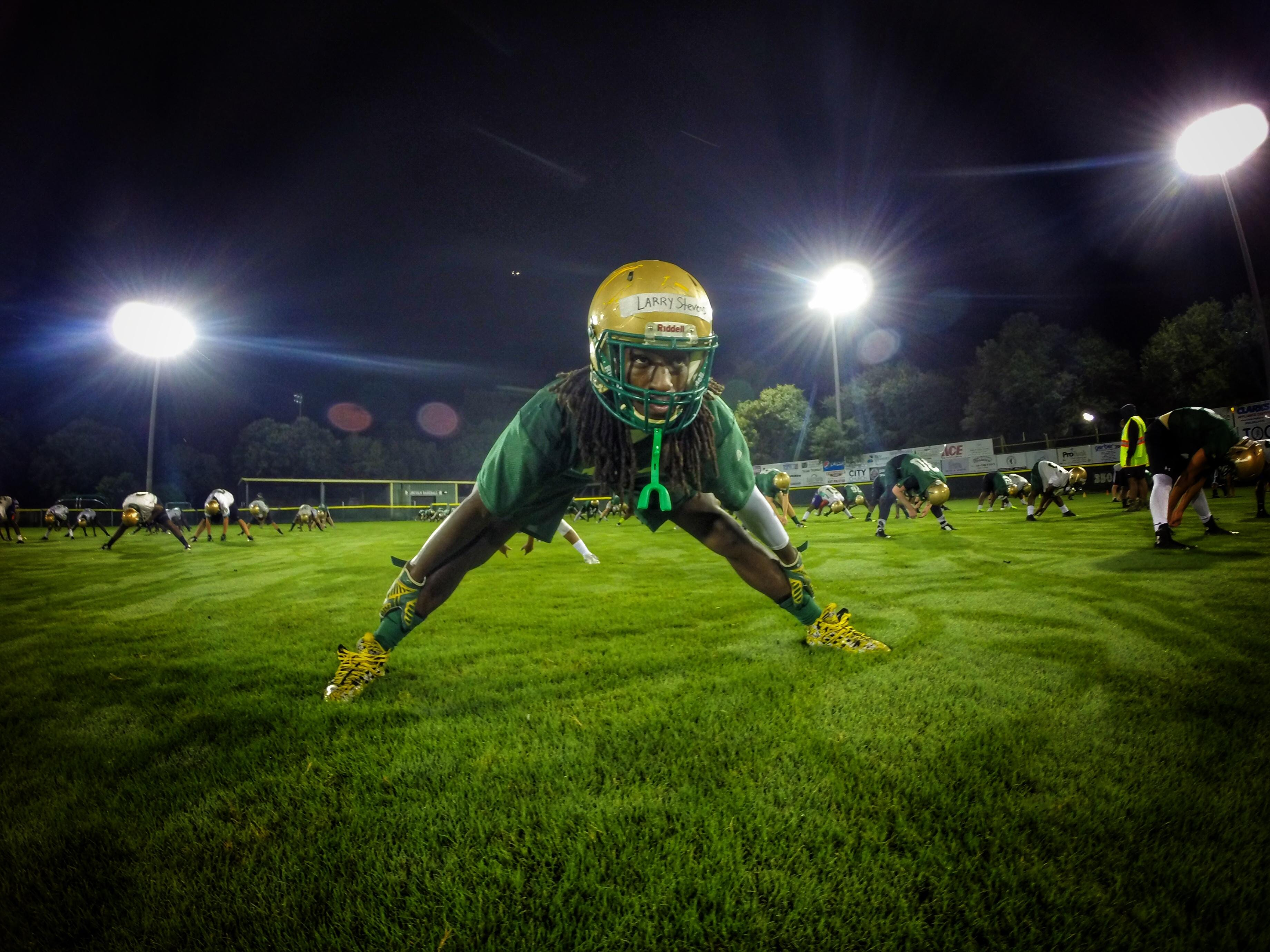 Lincoln defensive back Larry Stevens stretches with his teammates as part of the Trojans' Midnight Madness practice, a tradition since 1991 that marks the start of the fall football season.
