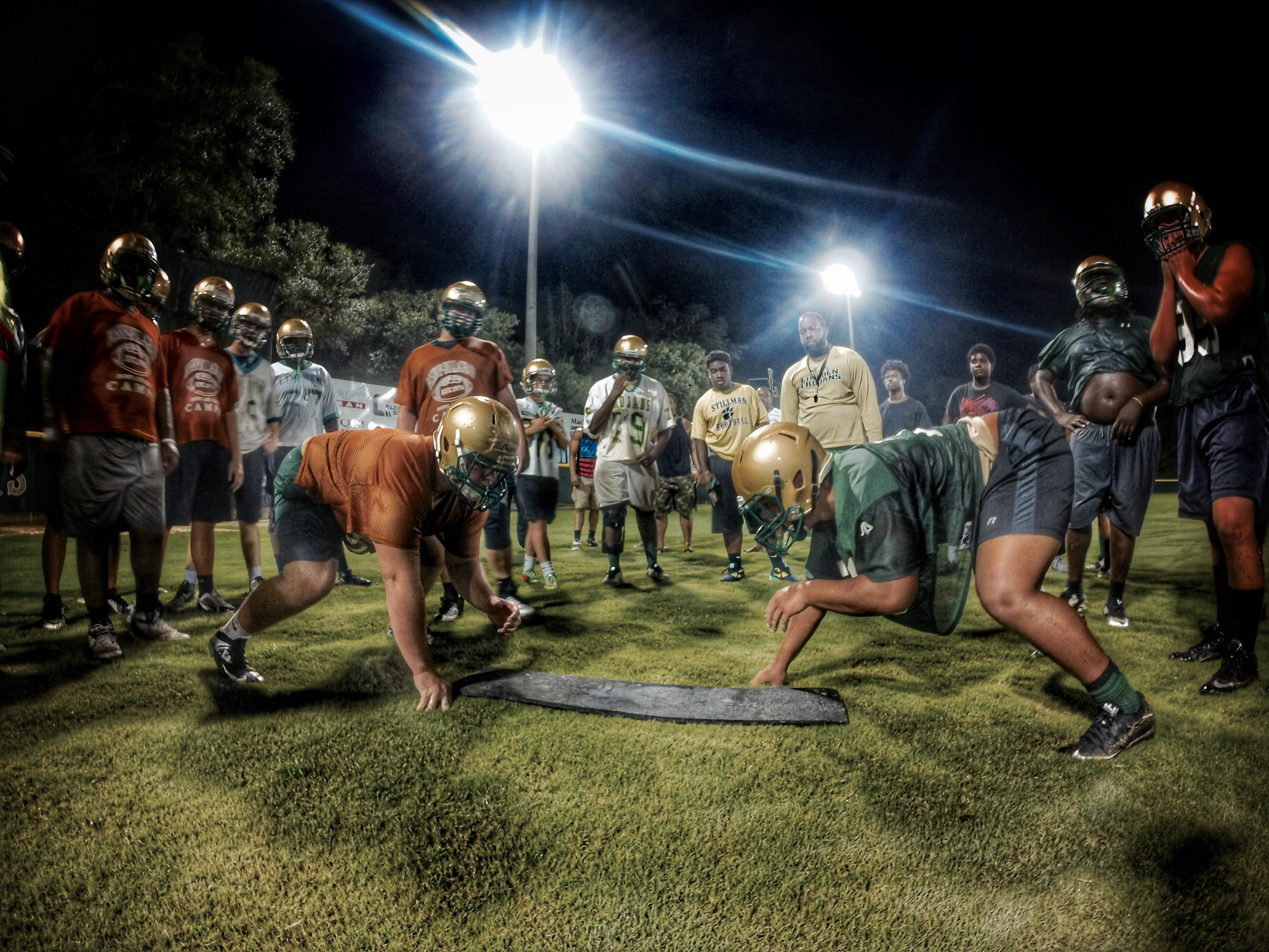 It's go time for Lincoln offensive lineman Tom Moss (left) as he gets ready for a contact drill during the Trojans' Midnight Madness practice at 12:01 a.m. on Aug. 3, 2015.