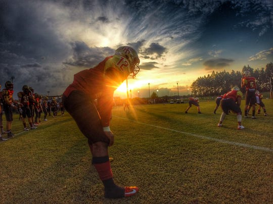 The sun sets on Florida High running back Makel Young and his Seminoles teammates as they run through warmups prior to a home game against East Gadsden.