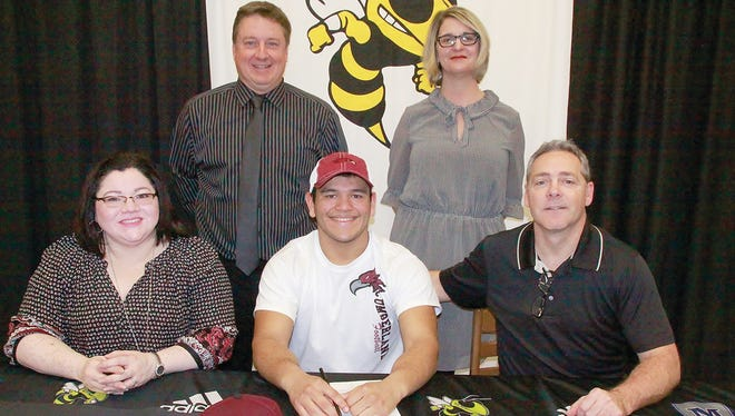 Proud parents James and Lillian Derrick, Head Coach Chris Hughes and Principal Juli Oyer observe Fairview High's Josh Ortiz-Derrick signing to play college football at Cumberland University.