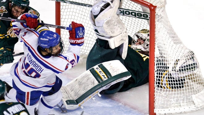 Vermont goalie Brody Hoffman is knocked back into the net after colliding with UMass Lowell forward John Edward (29) during the third period of the Hockey East semifinals in Boston on Friday.