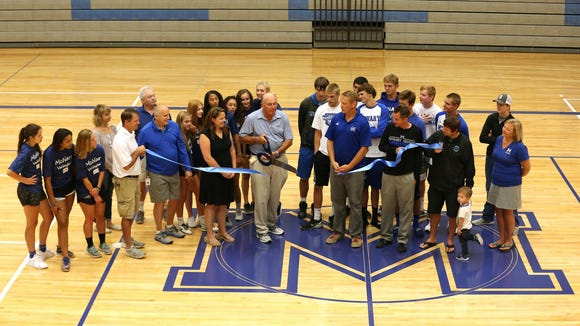 School officials and athletes representing volleyball, boys and girls basketball and wrestling unveil the new McNary High School gymnasium floor during a ceremony on Monday, Aug. 8, 2016, in Keizer. Athletic Director Ron Richards said the previous floor was about 20 years old. The new floor features a large M in the center of the floor, as well Keizer, OR and a mascot logo on the edges of the floor.