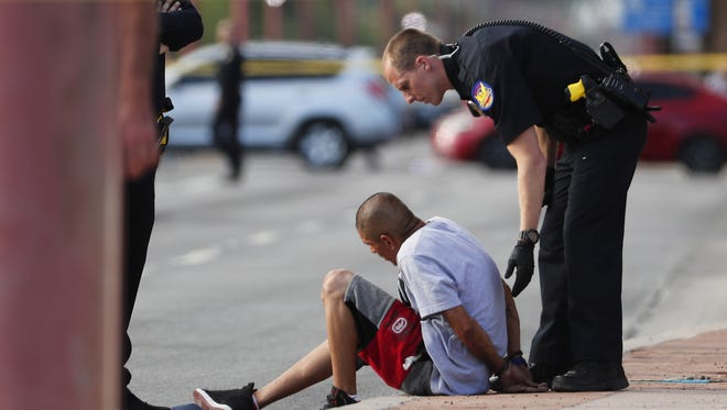 A Phoenix police officer stands with the victim of a robbery that led to an officer-involved shooting May 21, 2018, near Central Avenue and Willetta Street. The man was originally detained but later determined to have been the victim.