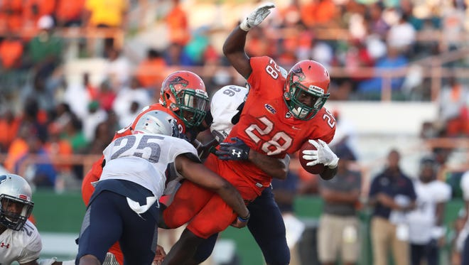 FAMU's Ricky Henrilus tries to squeeze through Howard defenders Leland Lassiter, left, and Taejuan Gray during their game at Bragg Memorial Stadium on Saturday, Nov. 4, 2017.