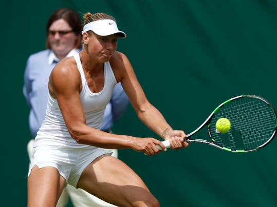 Belgium's Yanina Wickmayer plays a return to Australia's Samantha Stosur during their first round match at the All England Lawn Tennis Championships in Wimbledon, London,  Monday, June  23, 2014. (AP Photo/Sang Tan)