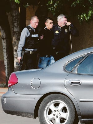 Police walk with 16-year-old Nathaniel Jouett, who was arrested Monday after a shooting spree at the Clovis public library.