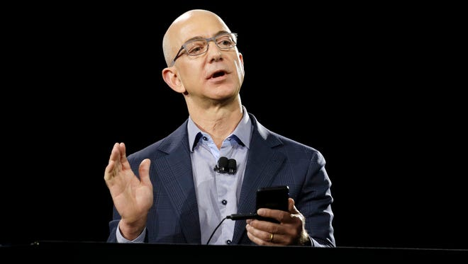File photo taken in 2014 shows Amazon CEO Jeff Bezos demonstrating the company's Fire Phone, in Seattle.