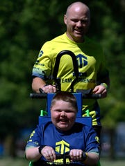 Devin Argall, 14, who has Muscular Dystrophy, teams with his father, Josh, to practice running at the Mariners Trail on Wednesday, July 20. Devin is the Wisconsin Goodwill Ambassador for the Muscular Dystrophy Association and the father and son pair particpate in many running events.